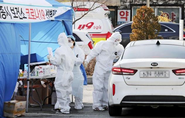 車に乗せたまま、乗員の新型コロナウイルス感染検査をする診療所の当局者=韓国・世宗市(聯合=共同)