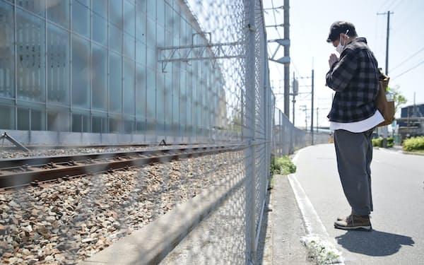 脱線事故で高校の同級生を亡くし、手を合わせる男性(25日、兵庫県尼崎市)