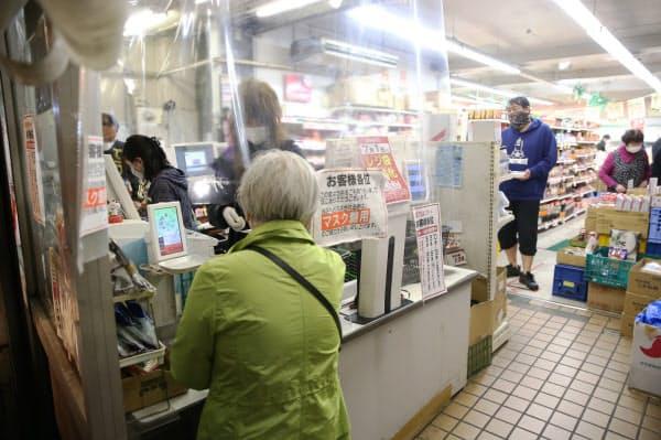 感染予防のため、スーパーのレジにはビニールシートが張られ、一定の距離を保つように並ぶ位置も離されていた(25日午後、東京都墨田区の「スーパーイズミ」)
