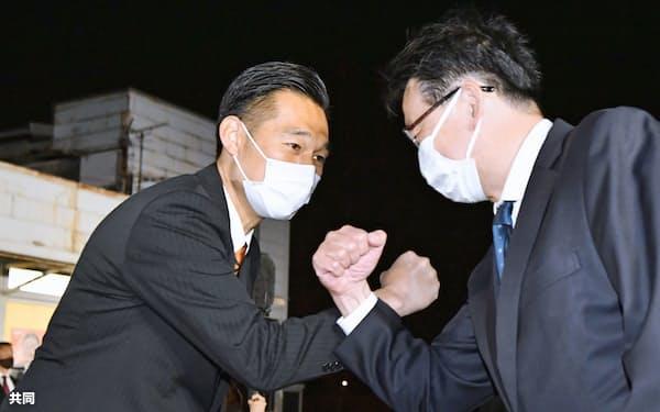 衆院静岡4区補欠選挙で初当選を決めた自民党の深沢陽一氏(左)。握手の代わりに腕を合わせた(26日、静岡市)=共同