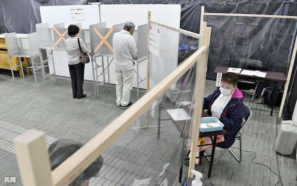 投票所では有権者と選管担当者との間に透明のシートが設置された(26日、静岡市)=共同