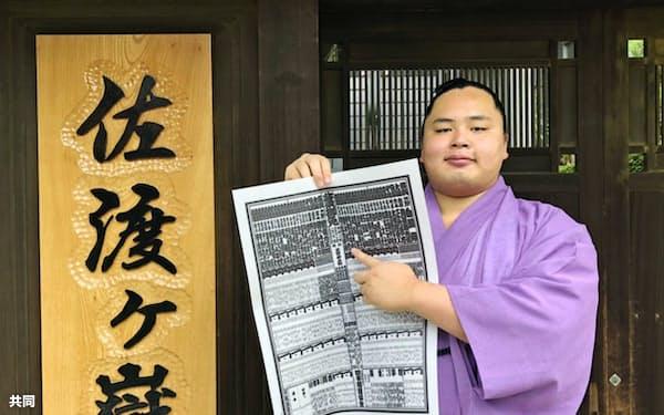 大相撲夏場所の番付表で、自らのしこ名を指さす新入幕の琴勝峰(27日、千葉県松戸市)=共同