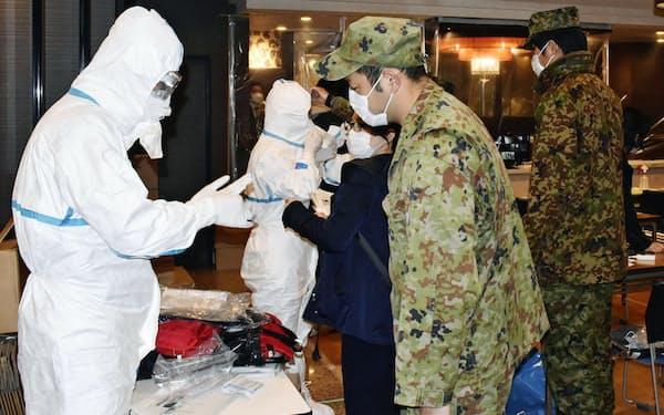 ホテルで無症状や軽症の新型コロナウイルス感染者の受け入れ準備をする自衛隊員(右側)(15日、さいたま市)=共同