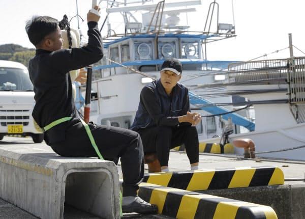一本釣りの指導をする岡本さん(右)。海と陸で1年の大半を共に過ごす実習生は「日々の成長が楽しみな息子のようだ」(3月、高知県土佐市)