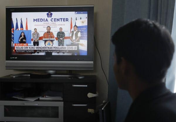 実習生の寮で動画配信サイト「YouTube(ユーチューブ)」を見るストリヨさん。ニュースで伝えられる母国の新型コロナウイルスの拡大に母親を案じる(4月)