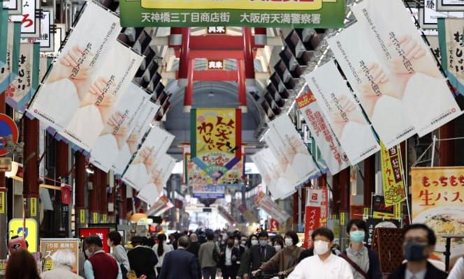 「新型コロナウイルスに負けない 私たちは人間だ」とのメッセージを掲げるのぼりが現れた天神橋筋商店街(28日、大阪市)=共同