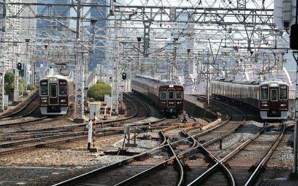 大阪梅田駅を同時に発車した京都線特急、宝塚線急行、神戸線特急(左から)がそろって十三駅に滑り込んでくる