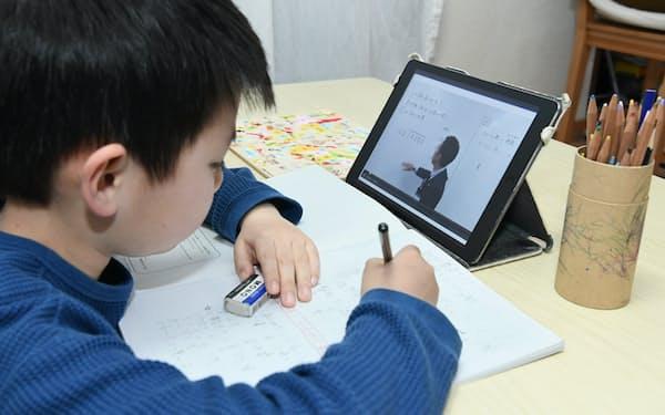 塾の動画配信を利用して、自宅で勉強する小学生