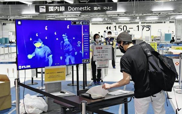 搭乗前にサーモグラフィーで体温確認を受ける利用客(1日午後、成田空港)=共同