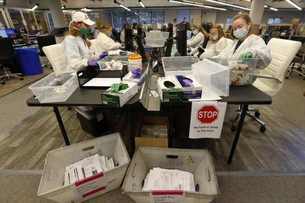 新型コロナウイルスの検査手続きを行う作業員ら(4月、米バージニア州リッチモンド)=AP