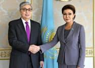 握手するカザフスタンのトカエフ大統領(左)とダリガ氏(2019年3月、アスタナ〈現ヌルスルタン〉)=AP