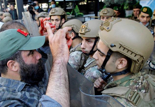 治安部隊と対峙するデモ参加者の男性(左)(1日、ベイルート)=ロイター