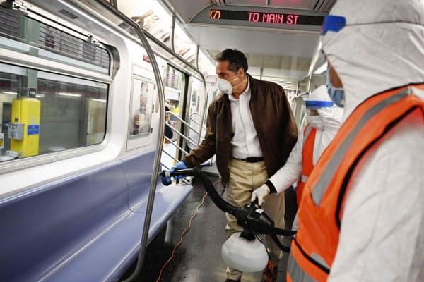 地下鉄の清掃に使われる道具を試すニューヨーク州のクオモ知事=AP
