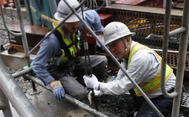 軽量の保護具などを身につけて工事現場で働く忠武建基の70代の社員(右)