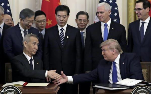 合意文書に署名し握手するトランプ米大統領(右)と中国の劉鶴副首相(1月、ワシントン)=AP