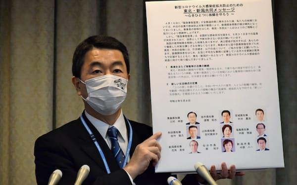 共同メッセージを掲げる宮城県の村井知事(8日、宮城県庁)