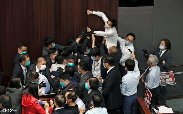 8日、香港立法会で民主派と親中派の議員がもみ合いになった=ロイター