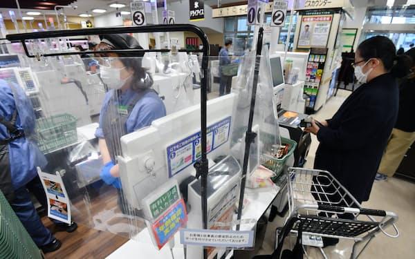ビニールカーテンで覆われたレジで働くスーパーの従業員(東京都杉並区のサミットストア西永福店)