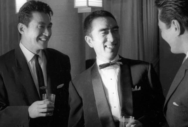 1960年、主演映画「からっ風野郎」の完成パーティーで談笑する三島由紀夫(中央)はタキシード姿。左は俳優の船越英二(東京都千代田区の帝国ホテル)=共同