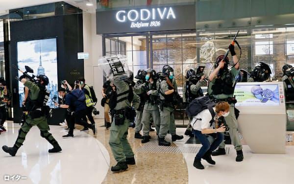 武装警察が商業施設に入り、デモを取り締まった(10日、香港)=ロイター