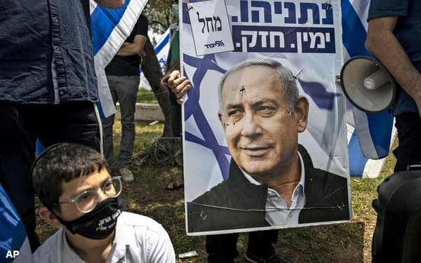 ネタニヤフ首相のポスターを掲げる支持者ら(3日、エルサレム)=AP