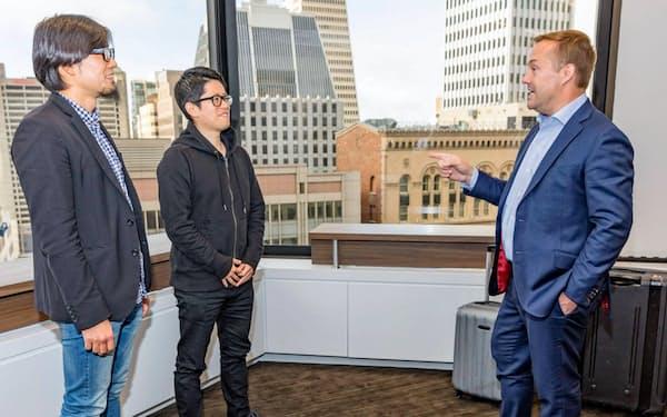 米エニープレイスの内藤聡最高経営責任者(CEO、中)と同社に投資したジェイソン・カラカニス氏(右)