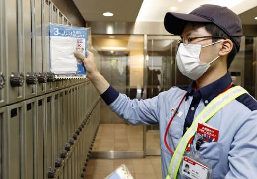 集合住宅のポストに布マスクを投函する郵便局員(12日午前、大阪市)=共同