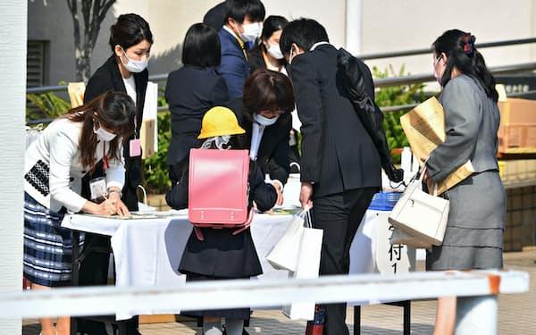 入学式の受け付けをする新入生と保護者ら(4月4日、大阪市浪速区の大国小学校)