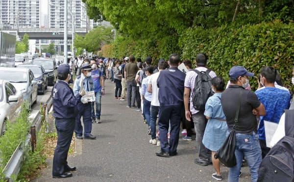東京出入国在留管理局の前に並ぶ大勢の在留外国人ら(12日、東京都港区)=共同