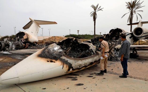 10日、トリポリの空港への砲撃で破壊された旅客機を調べるリビアの警察官=ロイター