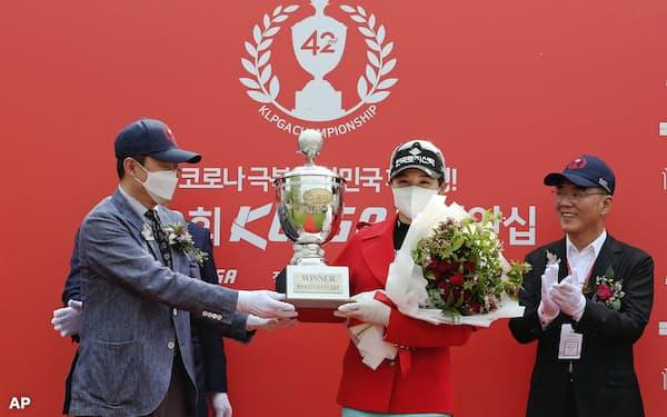 ゴルフの韓国女子プロ選手権で優勝し、マスク姿でトロフィーを受け取る朴ヒョンギョン(17日、韓国・楊州)=AP