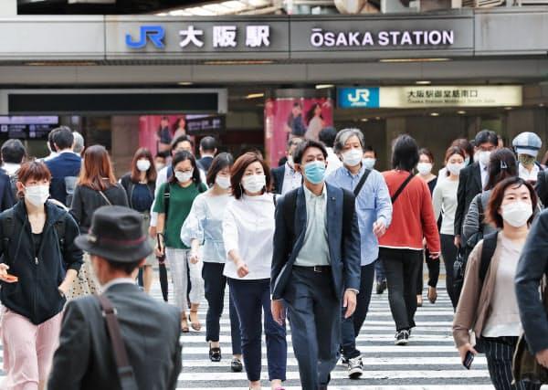 休業要請緩和後の週明け、出勤する人たちが行き交うJR大阪駅前(18日、大阪市北区)
