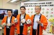 セブンイレブンが発売する親子丼など比内地鶏を使った商品を手に持つ関係者(18日、秋田県庁)