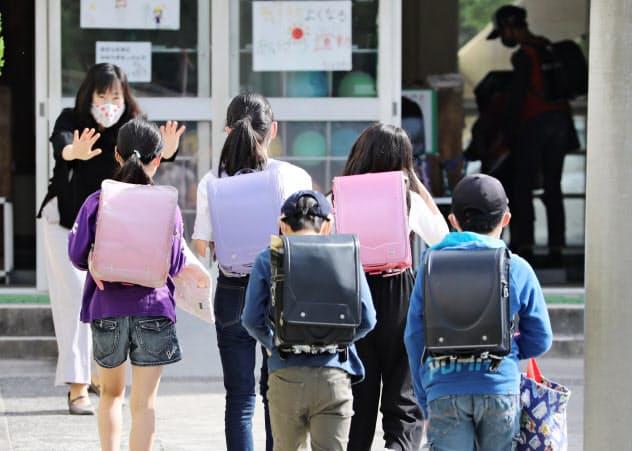 学校が再開し、登校する児童(18日、三重県桑名市の市立七和小学校)