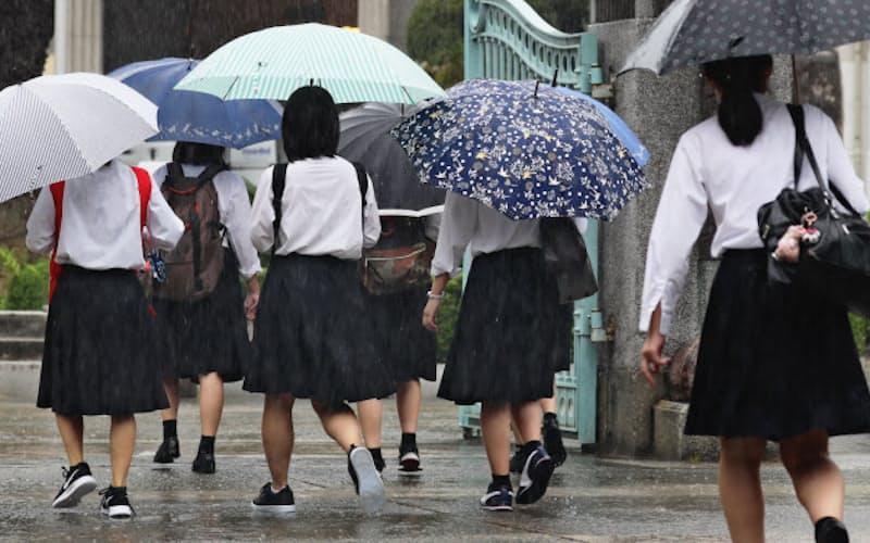 登校時間をずらして学校へ向かう県立福岡高校の生徒(18日、福岡市博多区)