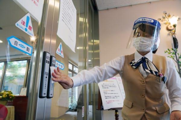 フェースシールドをつけて、自動ドアのボタンを消毒する病院のスタッフ(18日、埼玉県幸手市)