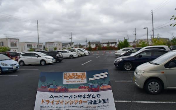 仮設スクリーンを設置する駐車場と開催チラシ(山形市のムービーオンやまがた)