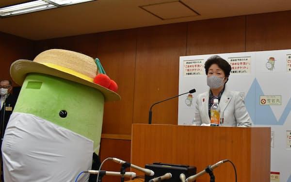 マスクをした県のキャラクターと記者会見する山形県の吉村美栄子知事(19日、県庁)