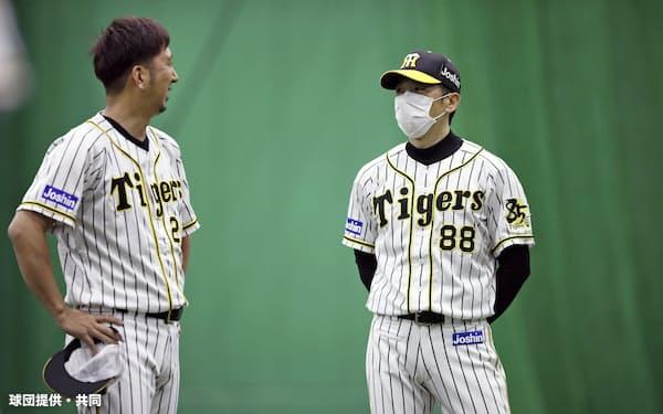 マスクを着け、甲子園の室内練習場で藤川(左)と話す阪神の矢野監督(19日)=球団提供・共同