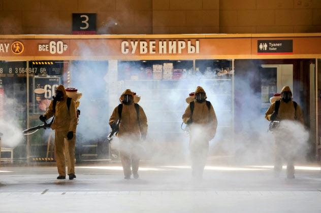 新型コロナの感染拡大でロシア経済の打撃が深まっている(18日、モスクワの鉄道駅での消毒)=ロイター