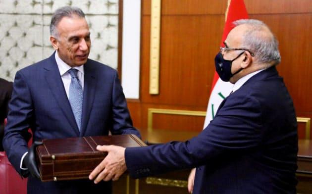 アブドルマハディ前首相(右)から引き継ぎを受けるカディミ新首相(5月7日、イラク議会報道室提供)=ロイター