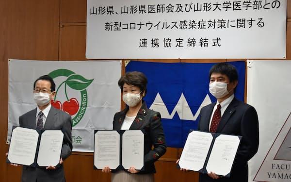 協定を結んだ山形大の上野医学部長(右)、吉村知事と中目県医師会長(21日、県庁)
