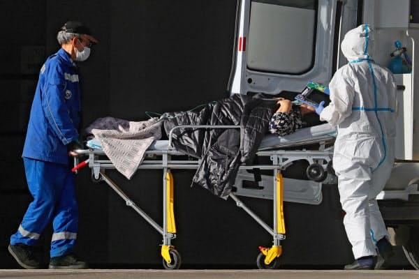 19日、モスクワで新型コロナ対応の医療施設に患者を運び込む救急隊員(タス通信=共同)