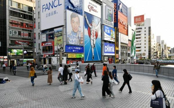 緊急事態宣言の解除が正式表明された大阪の繁華街を歩く人たち(21日、大阪市中央区)