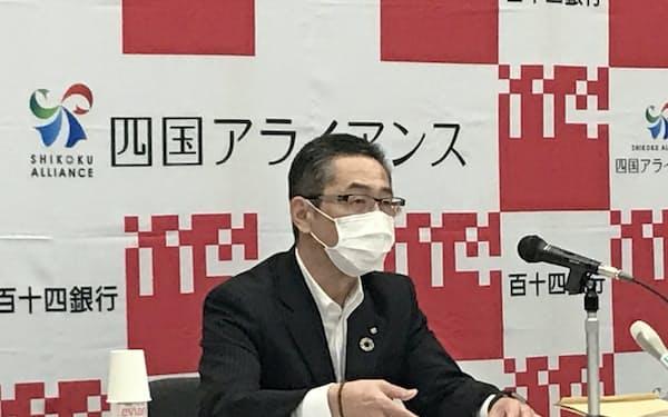 記者会見する百十四銀行の綾田頭取(15日、高松市内の本店)