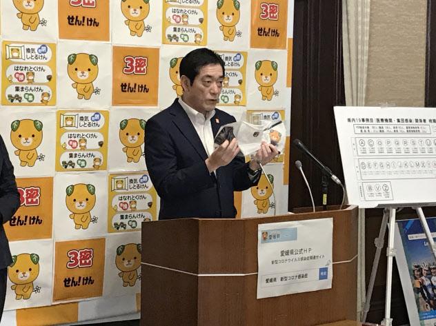 「みきゃんマスク」を掲げる中村時広・愛媛知事(21日、県庁)