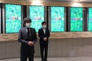 静岡市の中山間地域の木材を使ったデジタルサイネージの前で事業を発表する今田智久社長(左)と田辺信宏市長(15日、静岡市)
