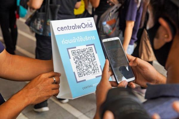 商業施設の出入り口でQRコードを読み取り、入退店の時間を記録する(17日、バンコク)=小高顕撮影