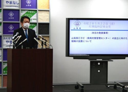 「山梨版CDC」について説明する長崎幸太郎知事(22日、甲府市内)
