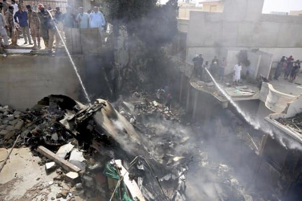 22日、パキスタン・カラチの旅客機墜落現場で、消火活動に当たる消防隊員=AP共同